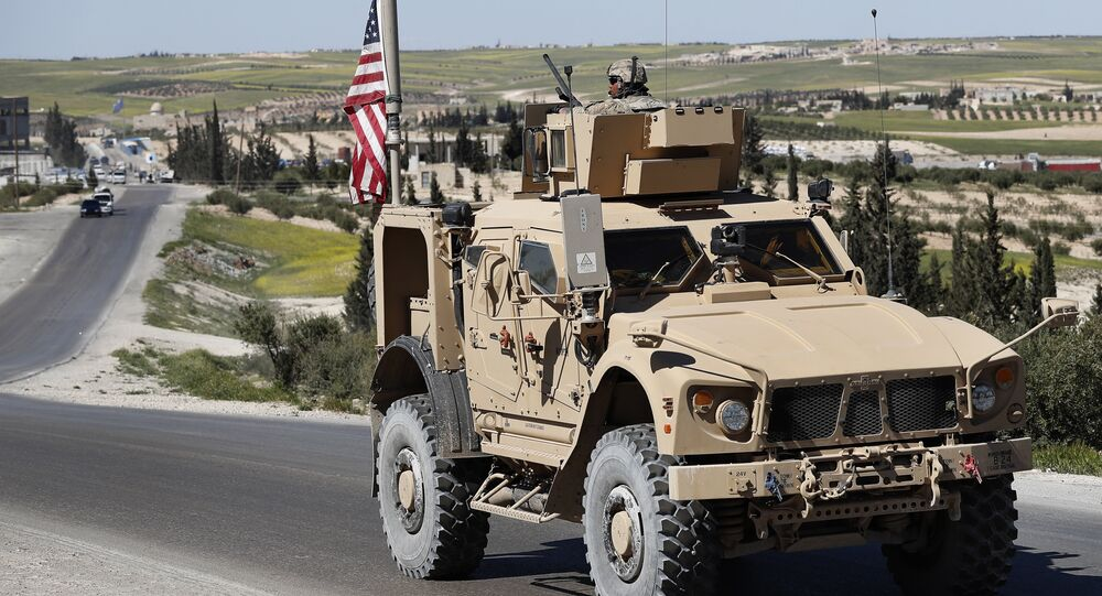 A U.S. soldier sits on an armored vehicle on a road leading to the tense front line with Turkish-backed fighters, in Manbij, north Syria, Wednesday, April 4, 2018