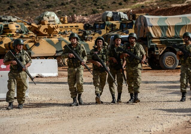 Turkish soldiers stand near armoured vehicles during a demonstration in support of the Turkish army's Idlib operation near the Turkey-Syria border near Reyhanli, Hatay, on October 10, 2017