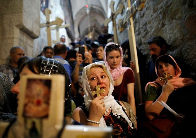 Worshippers hold crosses as they take part in the Good Friday procession in the Church of the Holy Sepulchre in Jerusalem's Old City April 6, 2018
