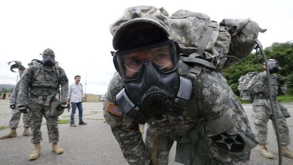 A soldiers of the U.S. Army 23rd chemical battalion wearing a gas mask rests after a competition at Camp Stanley in Uijeongbu, South Korea, Wednesday, July 8, 2015 - Sputnik International