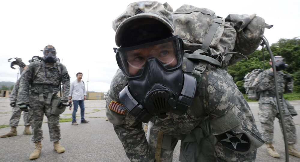 A soldiers of the U.S. Army 23rd chemical battalion wearing a gas mask rests after a competition at Camp Stanley in Uijeongbu, South Korea, Wednesday, July 8, 2015