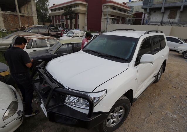 Pakistani journalists examine a car of American diplomate parked inside a police station after an accident in Islamabad, Pakistan, Saturday, April 7, 2018. Pakistani police say a car carrying an American diplomat has accidentally hit a Pakistani motorcyclist in the capital, Islamabad, killing him on the spot