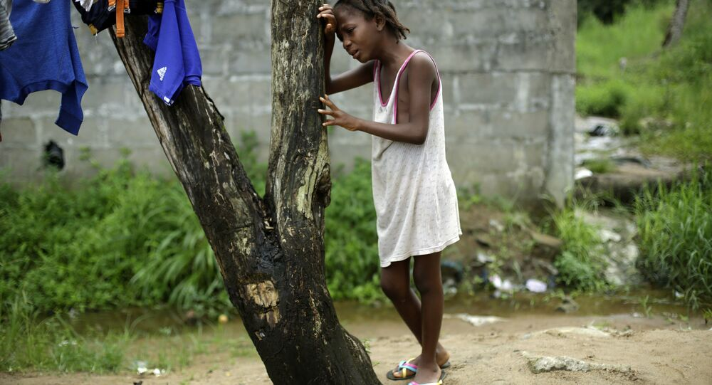 A child cries as community activists approach her outside her home in Liberia, a day after her mother was taken away by an ambulance to an Ebola ward,