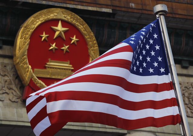 FILE - In this 9 November 2017 file photo, an American flag is flown next to the Chinese national emblem during a welcome ceremony for visiting US President Donald Trump outside the Great Hall of the People in Beijing