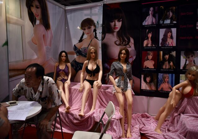 An exhibitor (L) speaks to a potential client at his adult sex toy doll stall at the Asia Adult Expo in Hong Kong on August 30, 2017