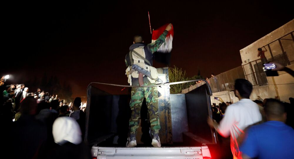 A member of forces of President Bashar al Assad holds a Syrian flag as buses carrying freed hostages and rebels who were evacuated from the rebel-held city of Douma drive at Wafideen camp in Damascus, Syria