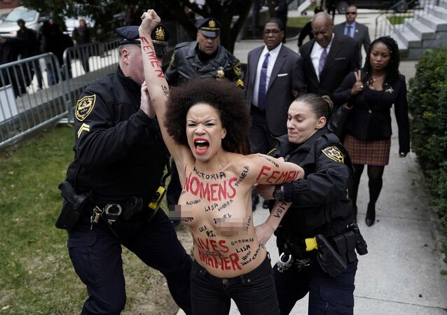 A protester is subdued by the police after breaking through the barriers, as actor and comedian Bill Cosby arrives for the first day of his sexual assault retrial at the Montgomery County Courthouse in Norristown, Pennsylvania, U.S