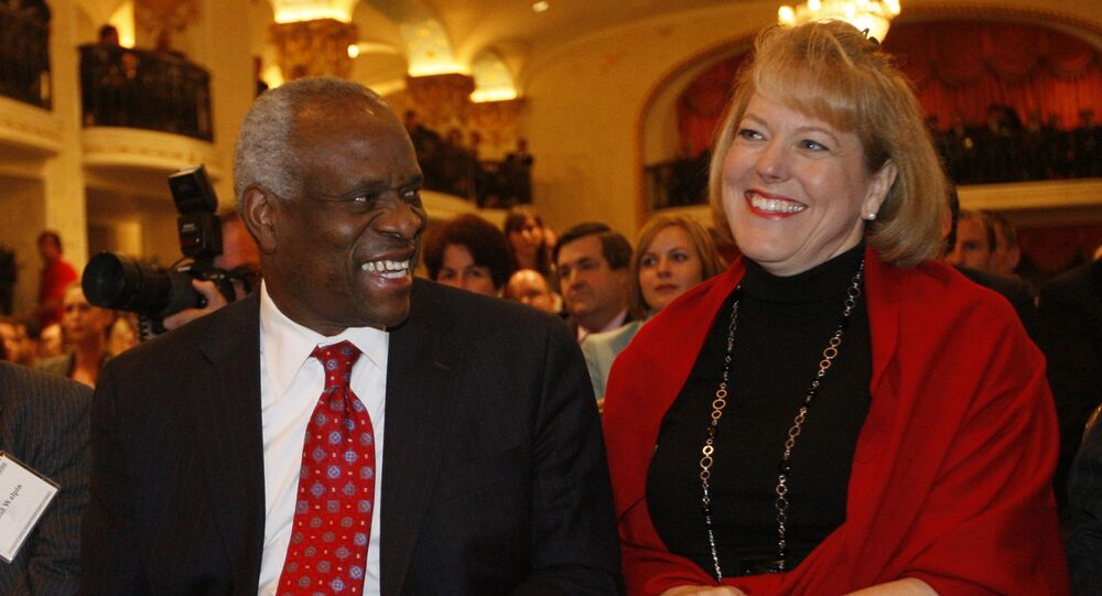 FILE - In this Nov. 15, 2007, photo, Supreme Court Justice Clarence Thomas, left, sits with his wife Virginia Thomas, as he is introduced at the Federalist Society in Washington, where he spoke about his new book and took questions from the audience.