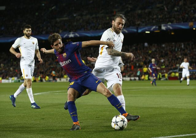 Barcelona's Sergi Roberto, left, challenges for the ball with Roma's Daniele de Rossi during a Champions League quarter-final, first leg soccer match between FC Barcelona and Roma at the Camp Nou stadium in Barcelona, Spain, Wednesday, April 4, 2018