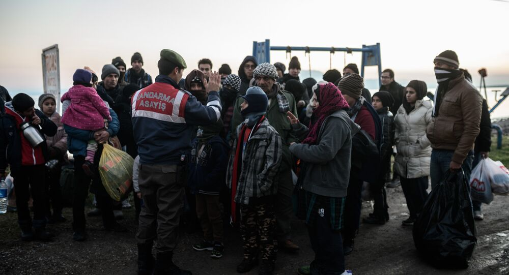 (File) Syrian and Afghan migrants and refugees wait after being caught by Turkish gendarme.
