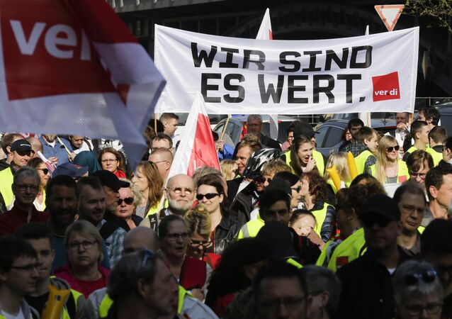 Members of the ver.di union with a banner reading: ' We are worth it.' attend a rally as part of a public sector pay strike in Berlin, Germany