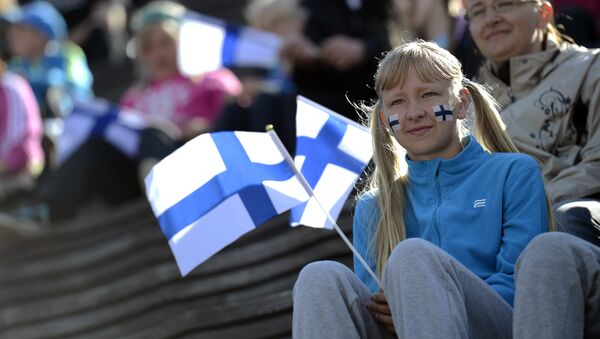 A girls holds a Finnish flag on the first day of the 2012 European Athletics Championships at the Olympic Stadium in Helsinki on June 27, 2012 - Sputnik International