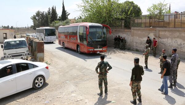 Pro-Syrian government forces gather around busses carrying Jaish al-Islam fighters and their families from their former rebel bastion of Douma as they arrive at the Syrian government-held side of the Wafideen checkpoint on the outskirts of Damascus, after being evacuated from the last rebel-held pocket in Estearn Ghouta on April 9, 2018 - Sputnik International