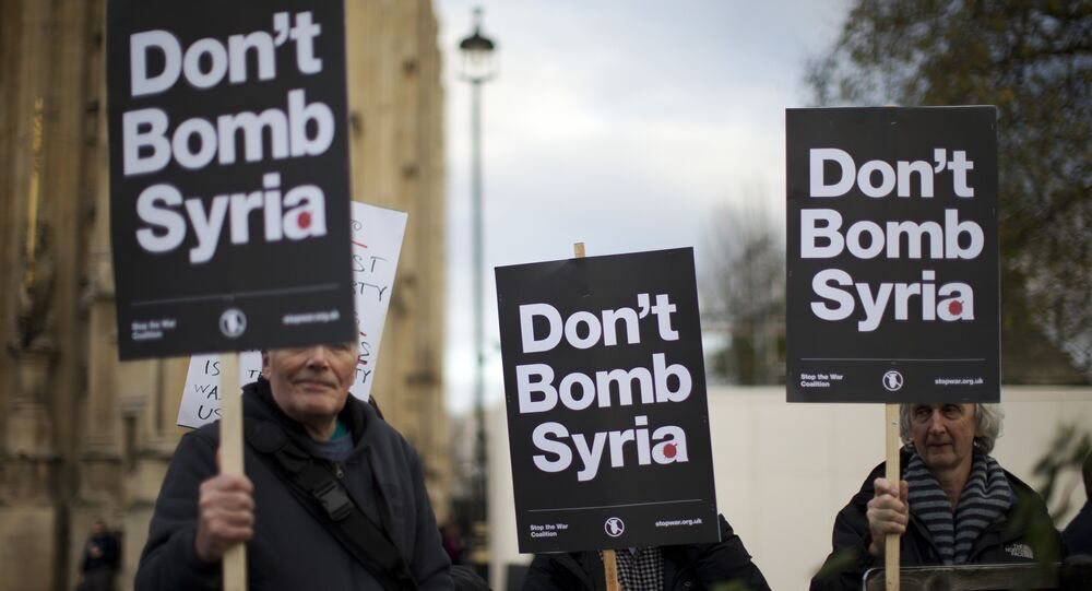 Supporters of the Stop the War Coalition hold placards protesting against Britain launching airstrikes against Islamic State extremists inside Syria, outside the Houses of Parliament as a debate goes on before a vote, Wednesday, Dec. 2, 2015.