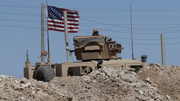 A U.S. soldier sits on an armored vehicle behind a sand barrier at a newly installed position near the tense front line between the U.S-backed Syrian Manbij Military Council and the Turkish-backed fighters, in Manbij, north Syria, Wednesday, April 4, 2018 - Sputnik International