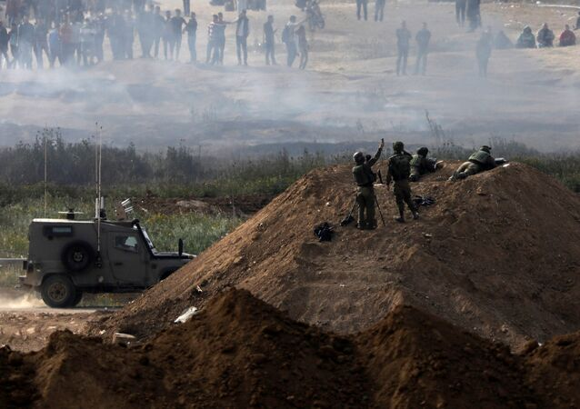 Israeli soldiers are seen next to the border fence on the Israeli side of the Israel-Gaza border, as Palestinians protest on the Gaza side of the border, Israel April 5, 2018