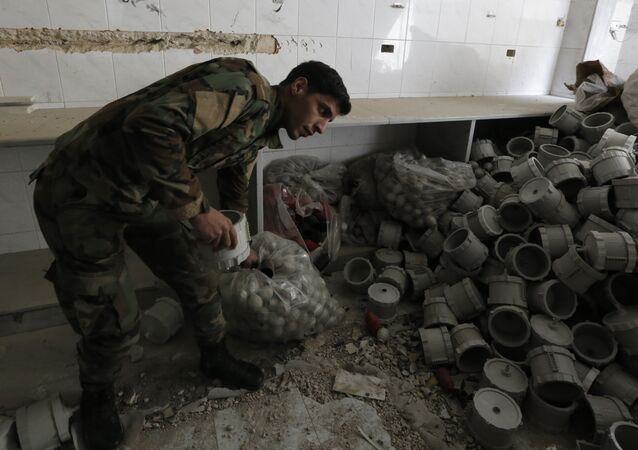 A member of the Syrian government forces looks at materials they say were used by opposition fighters to make weapons in the former rebel-held town of Zamalka in Eastern Ghouta, on the outskirts of the capital Damascus on April 11, 2018