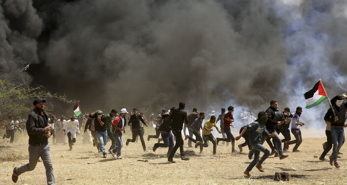 Palestinian protesters run to cover from teargas fired by Israeli soldiers during clashes with Israeli troops along Gaza's border with Israel, east of Khan Younis, Gaza Strip, Friday, April 6, 2018