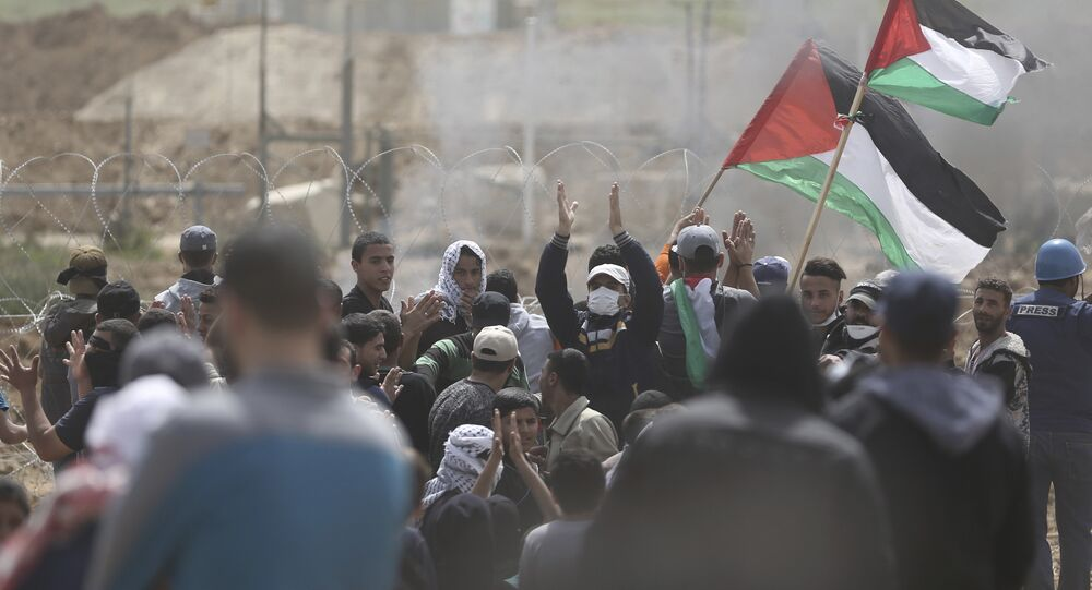 Palestinian protesters chant slogans as they gather during a protest at the Gaza Strip's border with Israel, Friday, April 13, 2018