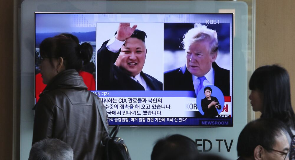 People pass by a TV screen showing file footages of U.S. President Donald Trump, right, and North Korean leader Kim Jong Un during a news program at the Seoul Railway Station in Seoul, South Korea, Monday, April 9, 2018