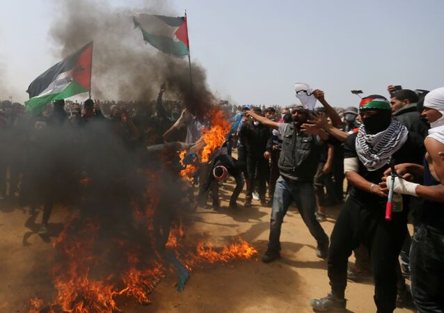 Palestinian demonstrators burn an Israeli flag during a protest demanding the right to return to their homeland, at the Israel-Gaza border, in the southern Gaza Strip, April 13, 2018