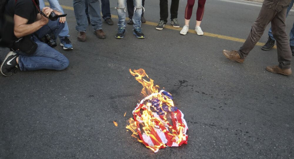 Protesters burn an American flag outside the U.S. Embassy in Athens, Friday, April 13, 2018, during a rally against possible western military intervention in Syria