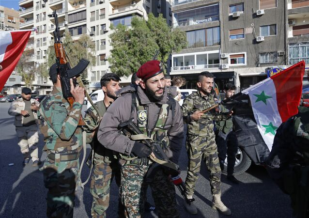Syrian soldier wave weapons and national flags as they chant slogans against U.S. President Trump during demonstrations following a wave of U.S., British and French military strikes to punish President Bashar Assad for suspected chemical attack against civilians, in Damascus, Syria, Saturday, April 14, 2018