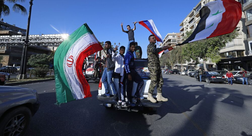 Syrian government supporters wave Syrian, Iranian and Russian flags as they chant slogans against US President Trump during demonstrations following a wave of US, British and French military strikes to punish President Bashar Assad for suspected chemical attack against civilians, in Damascus, Syria, Saturday, April 14, 2018.