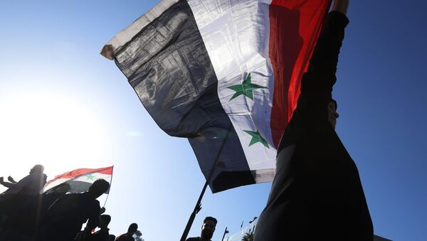 A Syrian government supporter holds up a Syrian national flag as he chants slogans against U.S. President Trump during demonstrations following a wave of U.S., British and French military strikes to punish President Bashar Assad for suspected chemical attack against civilians, in Damascus, Syria, Saturday, April 14, 2018 - Sputnik International