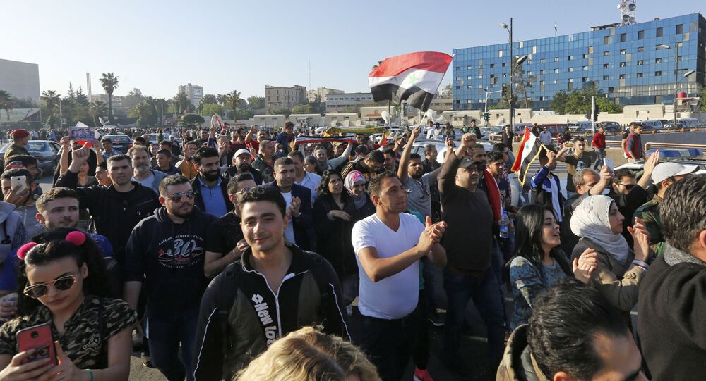 Syrians wave the national flag and wave portraits of President Bashar al-Assad as they gather at the Umayyad Square in Damascus on April 14, 2018, to condemn the strikes carried out by the United States, Britain and France against the Syrian regime