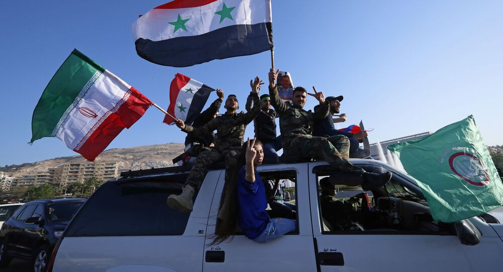 Syrian government supporters wave Syrian, Iranian and Russian flags as they chant slogans against US President Trump during demonstrations following a wave of U.S., British and French military strikes to punish President Bashar Assad for suspected chemical attack against civilians, in Damascus, Syria, Saturday, April 14, 2018