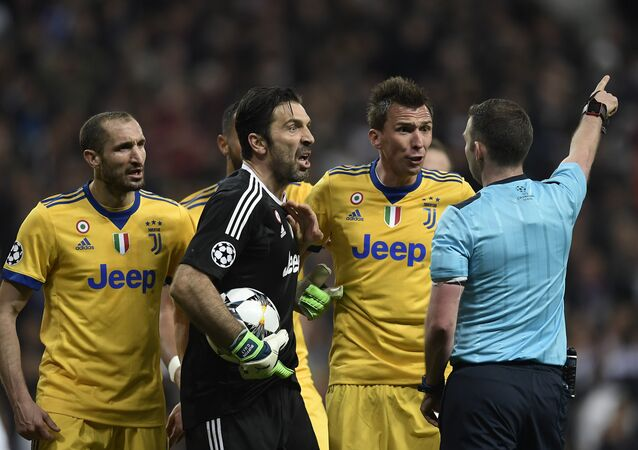 Juventus' Italian goalkeeper Gianluigi Buffon (2L) argues with the referee during the UEFA Champions League quarter-final second leg football match between Real Madrid CF and Juventus FC at the Santiago Bernabeu stadium in Madrid on April 11, 2018