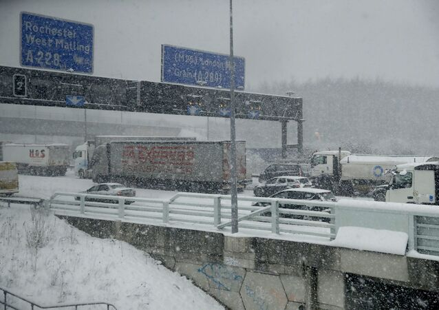 Vehicles crawl along a road as heavy snow falls in south east England