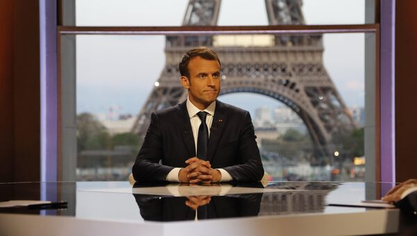 French President Emmanuel Macron poses on the TV set before an interview with RMC-BFM journalist Jean-Jacques Bourdin (R) and Mediapart investigative website journalist Edwy Plenel (L), at the Theatre National de Chaillot across from the Eiffel Tower in Paris, France, April 15, 2018 - Sputnik International
