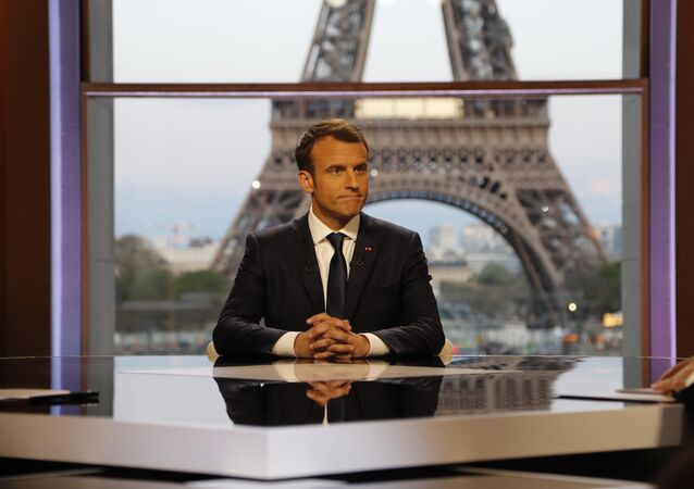 French President Emmanuel Macron poses on the TV set before an interview with RMC-BFM journalist Jean-Jacques Bourdin (R) and Mediapart investigative website journalist Edwy Plenel (L), at the Theatre National de Chaillot across from the Eiffel Tower in Paris, France, April 15, 2018