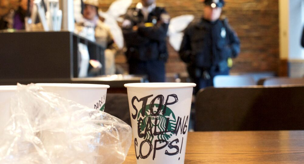 A Starbucks coffee cup with Stop Calling Cops! written on the side sits on a table as police monitor protestors demonstrating inside a Center City Starbucks, where two black men were arrested, in Philadelphia, Pennsylvania U.S., April 16, 2018.