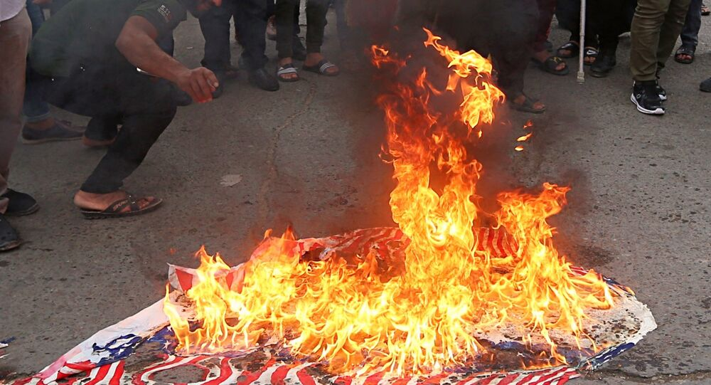 Protesters burn representations of US flags during a protest against the US-led missile attack on Syria, in Tahrir Square, Baghdad, Iraq, Sunday, April 15, 2018.
