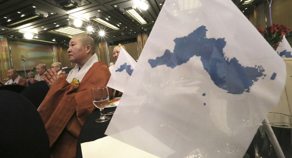 A woman Buddhist monk prays next to unification flags during the Peace Conference of World Buddhist Bhikkhunis for Reunification of North and South Korea in Seoul, South Korea, Thursday, April 12, 2018