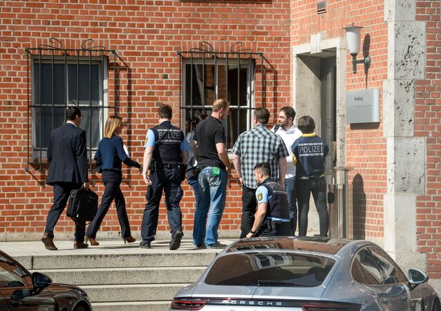 Policemen enter a building of German luxury car maker Porsche in Stuttgart, southern Germany