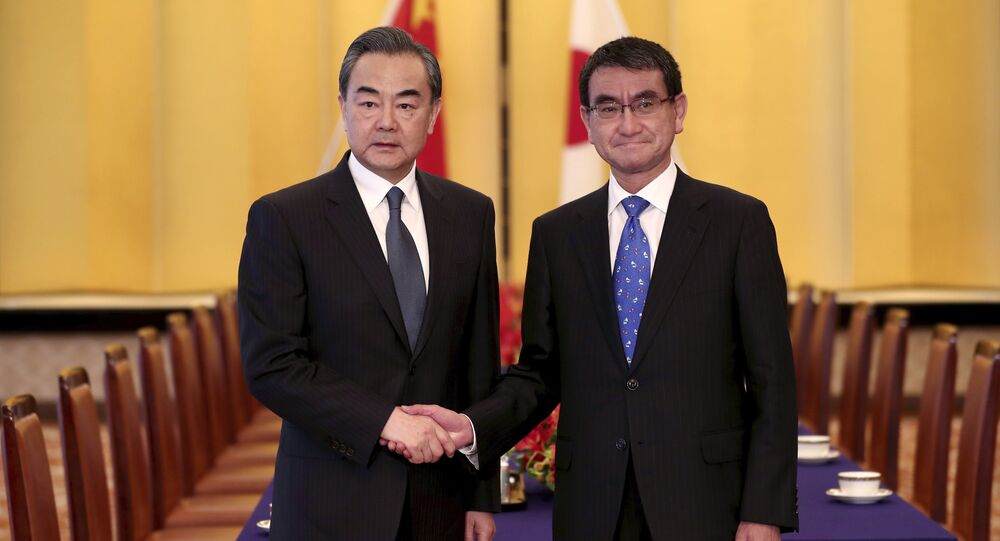 Japanese Foreign Minister Taro Kono, right, and his Chinese counterpart Wang Yi, left, shake hands ahead of their meeting in Tokyo