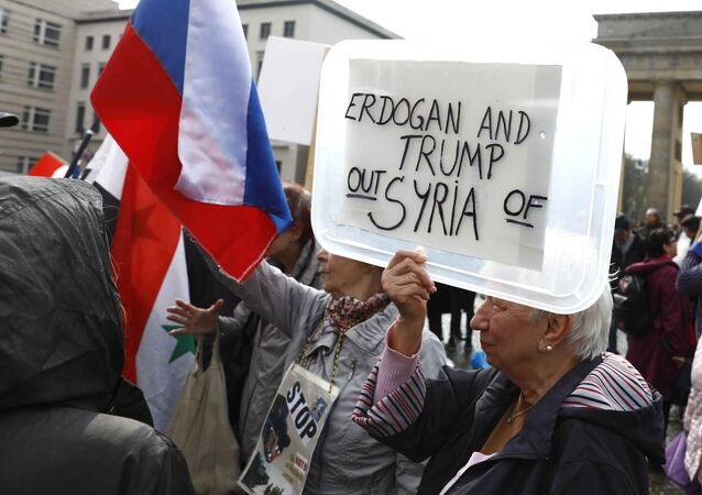 (File) A protester holds a poster during the demonstration against airstrikes on Syria in Berlin, Germany April 14, 2018