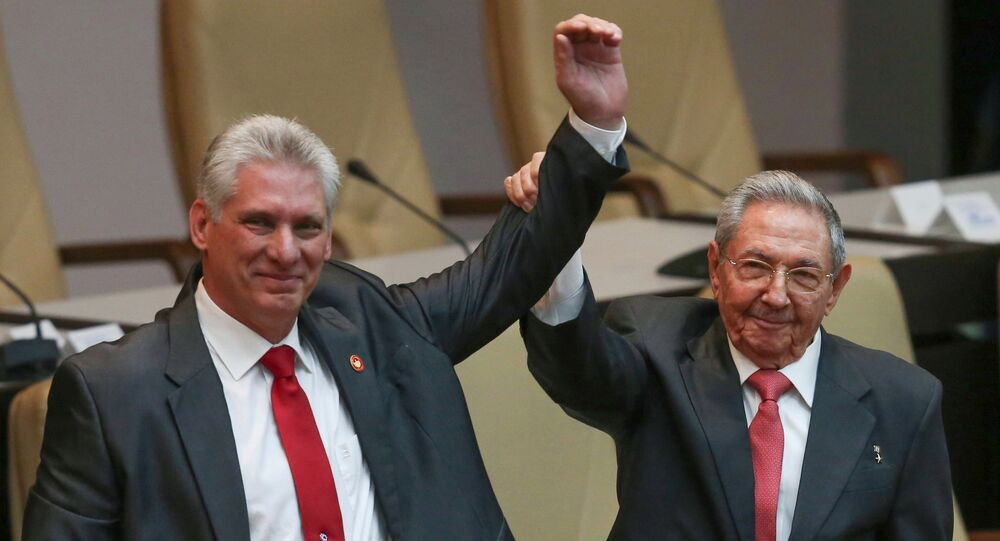 Cuba's outgoing President Raul Castro, right, and new President Miguel Diaz-Canel raise their arms in unison at the National Assembly in Havana, Cuba, Thursday, April 19, 2018.