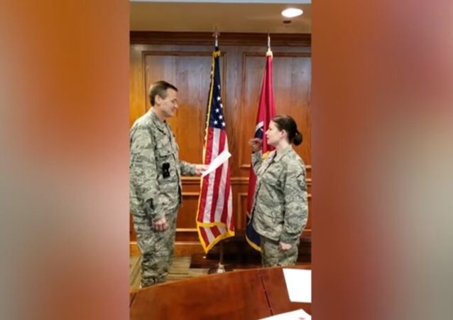 Tennessee Air National Guard recites her oath with a dinosaur puppet