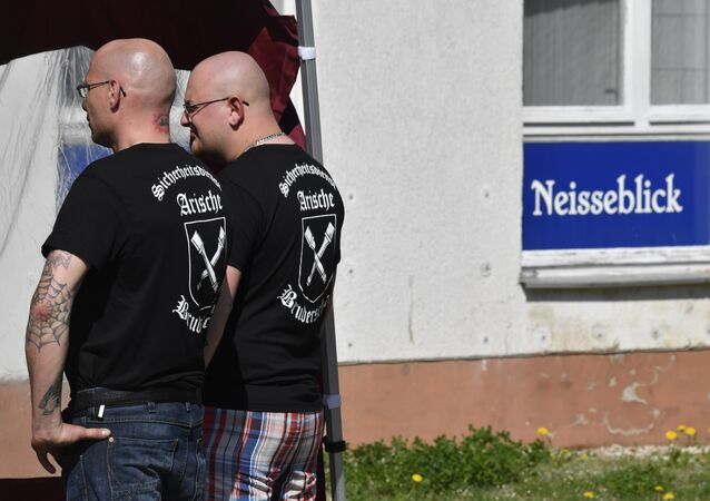 Private security personel with Aryan Brotherhood on their T-shirts stand guard at the venue of the Schild und Schwert (Shield and Sword) neo-nazi festival, in the small eastern German town of Ostritz