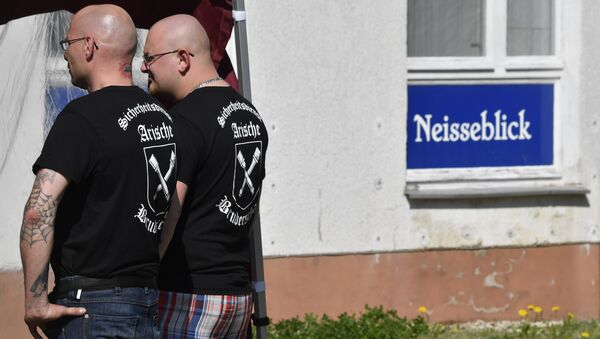 Private security personel with Aryan Brotherhood on their T-shirts stand guard at the venue of the Schild und Schwert (Shield and Sword) neo-nazi festival, in the small eastern German town of Ostritz - Sputnik International