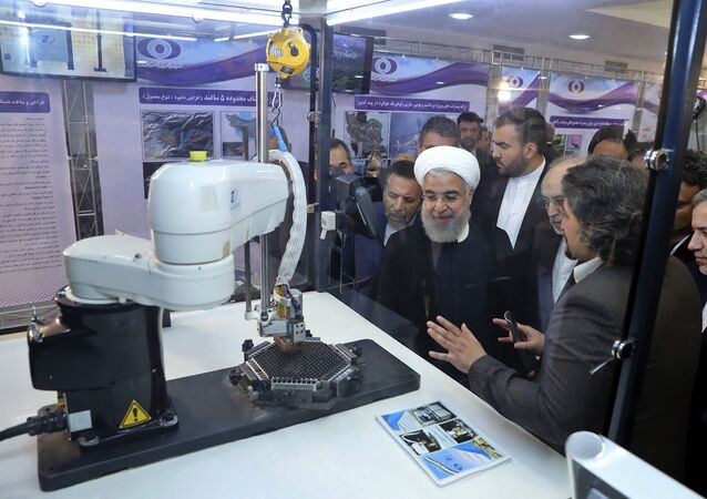 In this photo released by an official website of the office of the Iranian Presidency, President Hassan Rouhani listens to explanations on new nuclear achievements at a ceremony to mark National Nuclear Day, in Tehran, Iran, Monday, April 9, 2018