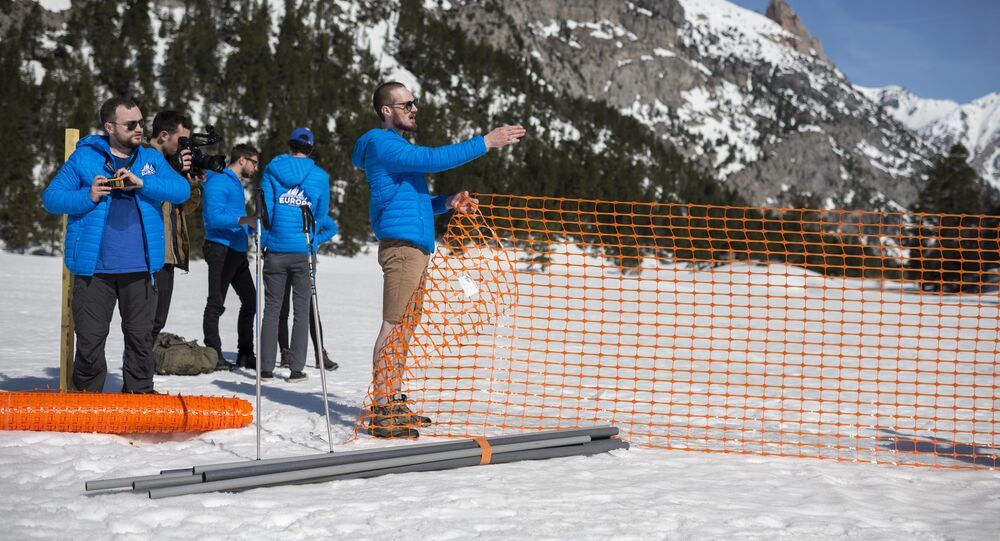 Activists from the French far-right political movement Generation Identitaire (GI) and European anti-migrant group Defend Europe erect a barrier during an operation titled Mission Alpes to control access of migrants using the Col de l'Echelle mountain pass on April 21, 2018 in Nevache, near Briancon, on the French-Italian border