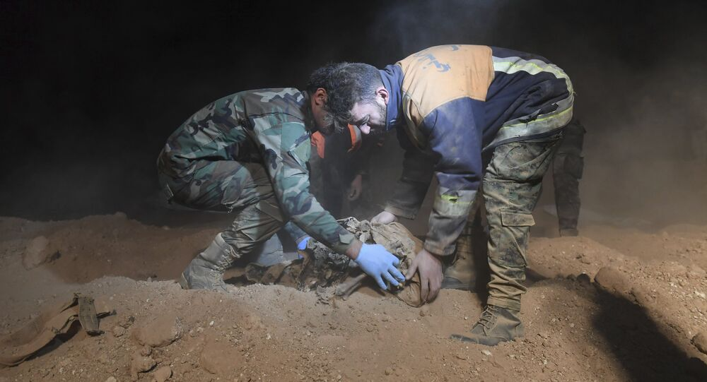 Syrian security forces members remove human remains at the site were discovered two mass graves believed to contain the bodies of civilians and troops killed by Daesh, in the village of Wawi near the northern city of Raqqa, Syria (File)
