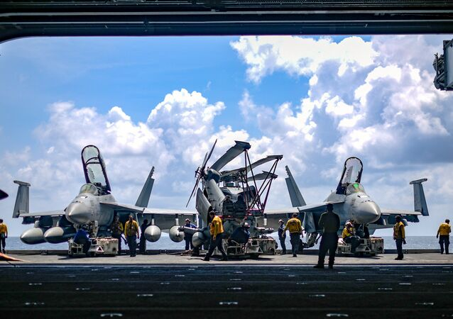 U.S. Navy sailors move aircraft from an elevator into the hangar bay of the aircraft carrier USS Theodore Roosevelt in the South China Sea April 8, 2018. Picture taken April 8, 2018