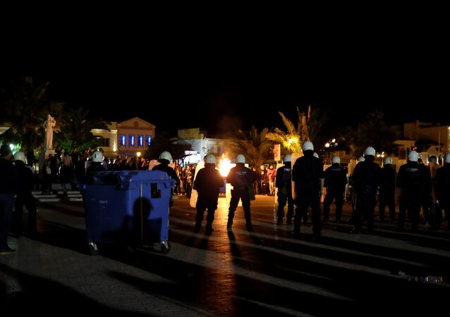 A garbage bin burns as riot police officers stand guard separating protesting groups of locals and refugees demonstrating against conditions in Moria camp and delays in asylum applications, in the city of Mytilene on the island of Lesbos, Greece, April 22, 2018
